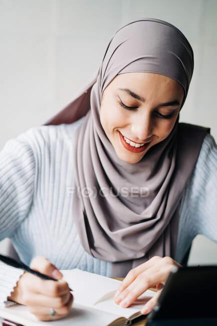 Щаслива мусульманка-фрилансер в традиційному головному шарфі сидить за столом і пише в блокноті під час роботи в кафе. — стокове фото