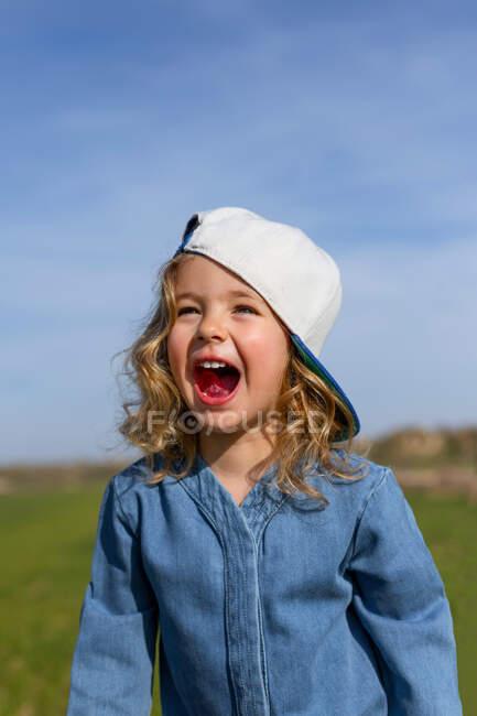 Счастливая блондинка в шапке смотрит прочь с открытым ртом на голубое небо летом на лугу — стоковое фото