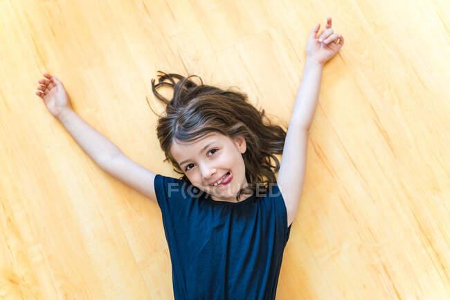 Вгорі виднілася радісна дівчинка, що лежала на паркеті з волоссям і руками, простягнутими й радісно сміючись, дивлячись на камеру. — стокове фото