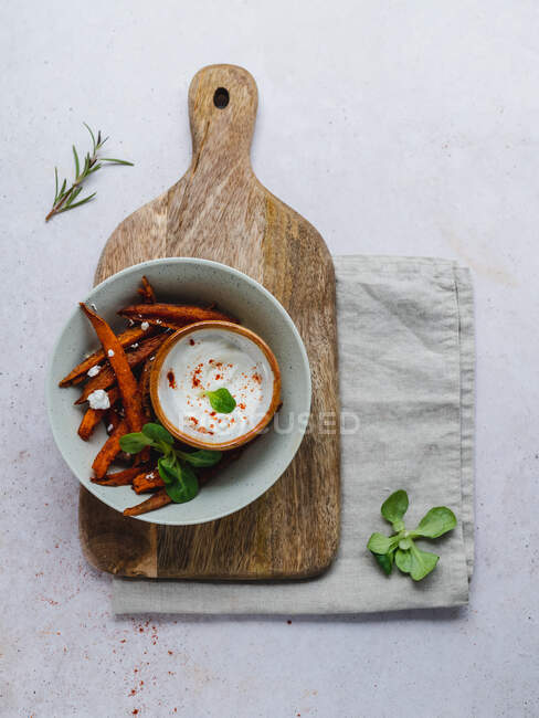 High angle of delicious sweet potato fries with sour cream and herbs served on table — Stock Photo