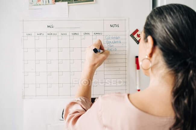 Back view of anonymous female taking notes in calendar on fridge with magnets while making plans in kitchen at home — Stock Photo