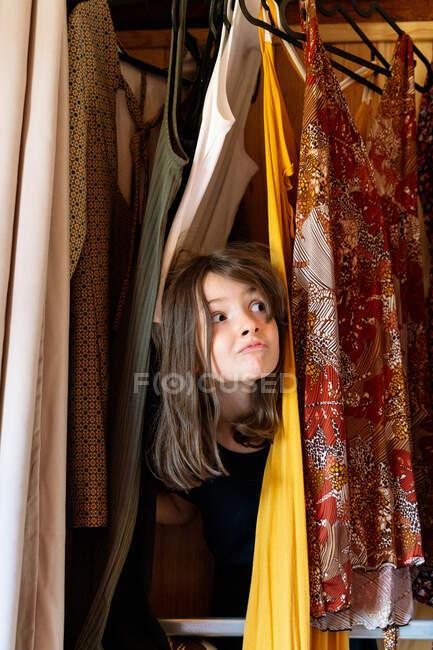 Menina brincalhão bonito escondendo em meio a vestidos pendurados em guarda-roupa enquanto olha para longe e sorrindo — Fotografia de Stock