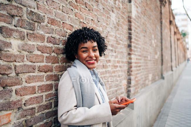 Приємна афро - американська жінка з кучерявим волоссям, що стоїть навпроти цегляної стіни та мобільного телефону. — стокове фото