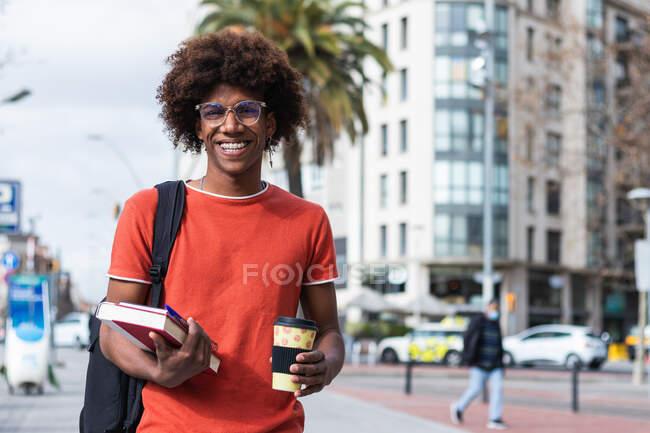 Щасливий молодий афроамериканець у повсякденному одязі та окулярах, який ходить по міській вулиці з книжками та бере каву в руки. — стокове фото