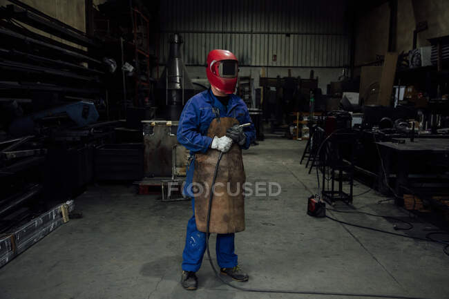 Anonymous mechanic in protective helmet and apron on blue overall standing with welding hose in light workshop near metal constructions — Stock Photo