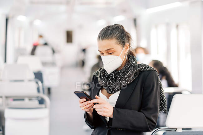 Serious female passenger wearing respirator text messaging on cellphone while standing in wagon with people on blurred background during journey — Stock Photo