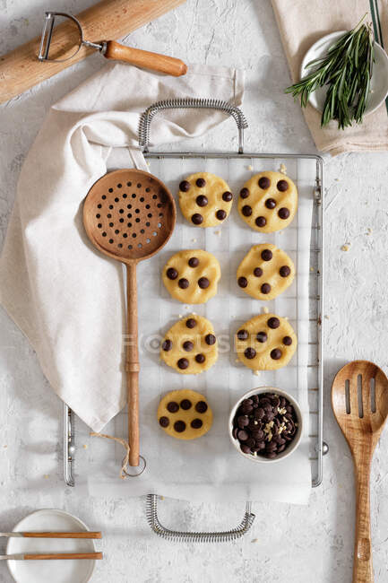Top view of freshly baked sweet cookies with chocolate chips on metal grid placed on table with various kitchen tools and green rosemary branches — Stock Photo