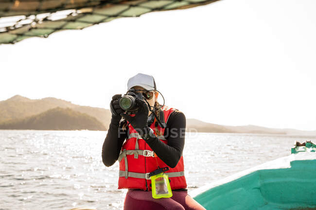 Touriste féminine joyeuse avec appareil photo numérique assis sur le bord du bateau pendant le voyage sur l'océan ondulé — Photo de stock