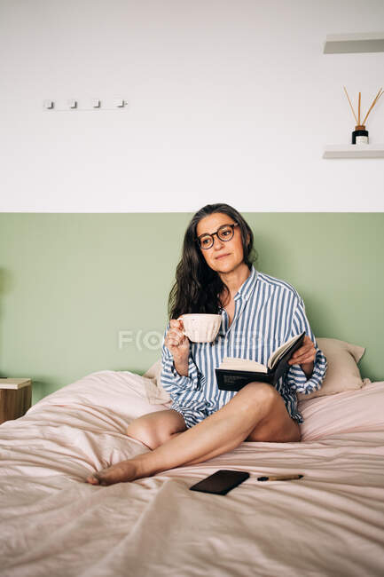 Clever female in eyeglasses with long hair and notebook looking away and resting on soft bed in bedroom — Stock Photo