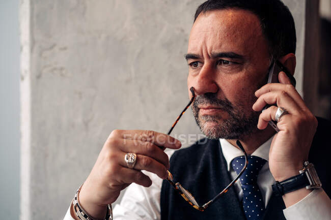 Crop upset middle aged Hispanic male entrepreneur with accessories speaking on cellphone while looking away in daytime — Stock Photo