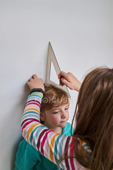 Sister helping brother with measuring him height with ruler and pencil near wall — Stock Photo