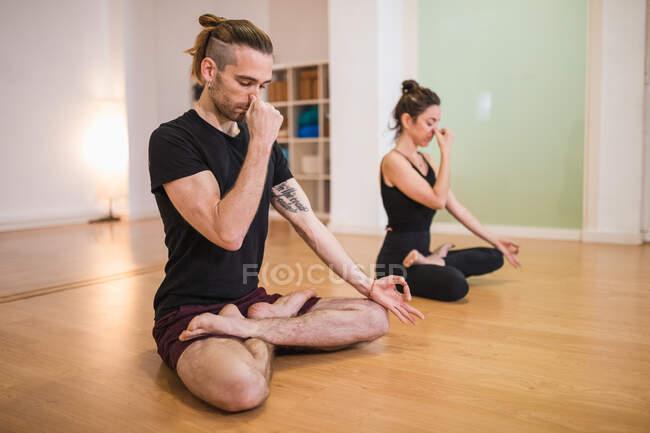 Полное тело босоногого тренера и женщины с закрытыми глазами, щипающими носы во время практики Падмасаны и медитирующей в студии — стоковое фото