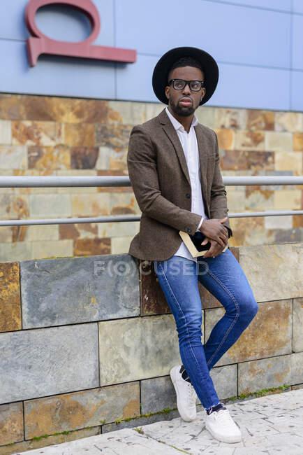 Hombre afroamericano con elegante sombrero y chaqueta de pie en la calle de la ciudad y libro de celebración - foto de stock