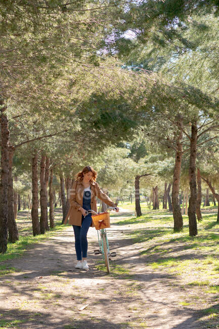 Full body of young female walking and concentrated near old bicycle with timber wicker basket in the park — Stock Photo