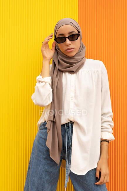 Mulher étnica legal em vestuário na moda e lenço de cabeça olhando para a câmera no fundo laranja e amarelo — Fotografia de Stock