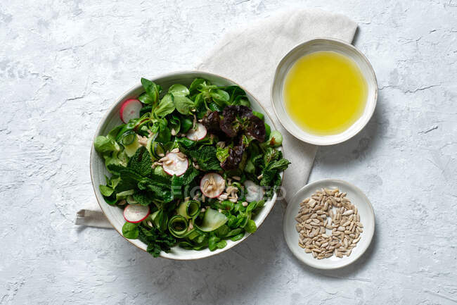 Top view of fresh healthy vegetable salad in bowl served on table with olive oil and sunflower seeds — Stock Photo