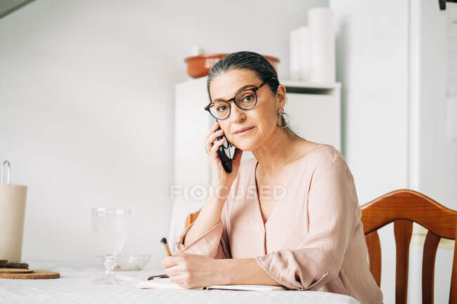 Serious middle aged female in eyeglasses having phone call and looking at camera while writing notes in notebook at table in room — Stock Photo
