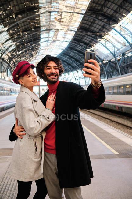 Vista lateral do casal alegre tomando auto retrato no celular na plataforma ferroviária — Fotografia de Stock
