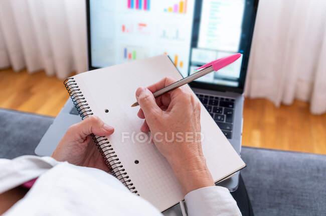 Desde arriba de la cosecha trabajadora anónima a distancia con bloc de notas y bolígrafo sentado en el sofá contra netbook con diagramas en pantalla - foto de stock