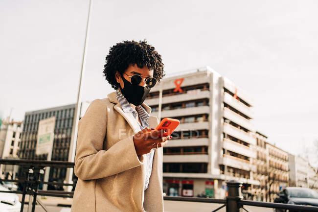 Desde abajo de la mujer afroamericana con estilo en mensaje de texto máscara de tela en el teléfono móvil mientras camina por la calle de la ciudad - foto de stock