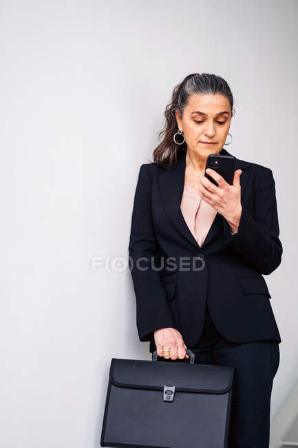 Serious middle aged female entrepreneur with ponytail wearing black suit text messaging on cellphone while standing on white background with folder — Stock Photo