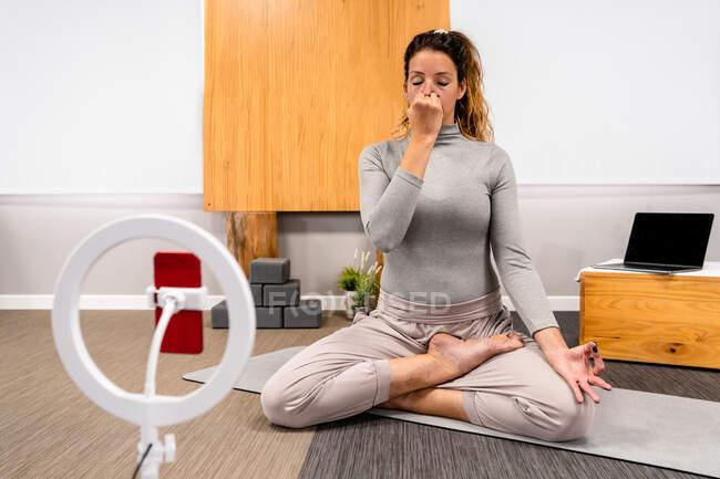 Тіло сконцентрованої молодої жінки в активаціях сидить в позі Лотоса з закритими очима і робить вправи для дихання Пранаями під час сеансу йоги вдома біля смартфона, поміщеного на тринозі. — стокове фото