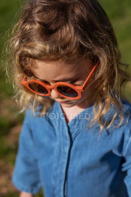 Високий кут милої щасливої дівчинки в модний одяг і сонцезахисні окуляри стоять і відпочивають на травиному газоні — стокове фото