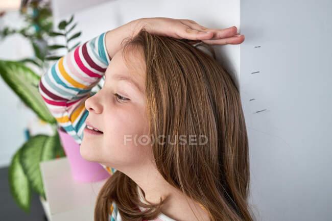 Vista lateral de la linda chica de pie cerca de la pared y midiendo su altura y mirando hacia otro lado - foto de stock