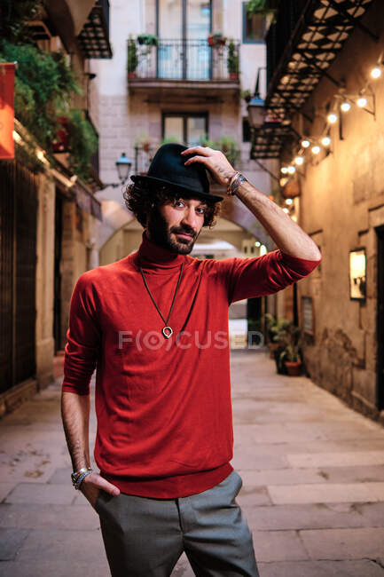 Adult bearded male in stylish wear with hand in pocket looking at camera on city street with glowing lights — Stock Photo