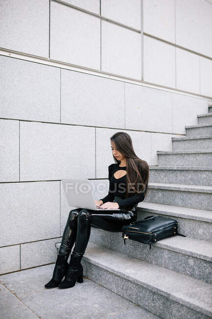 Side view of focused female entrepreneur sitting on stone steps in city and browsing netbook while working on project online — Stock Photo
