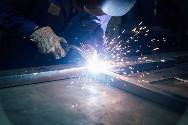 Crop faceless worker in gloves and uniform welding metal details on table near constructions in factory — Stock Photo