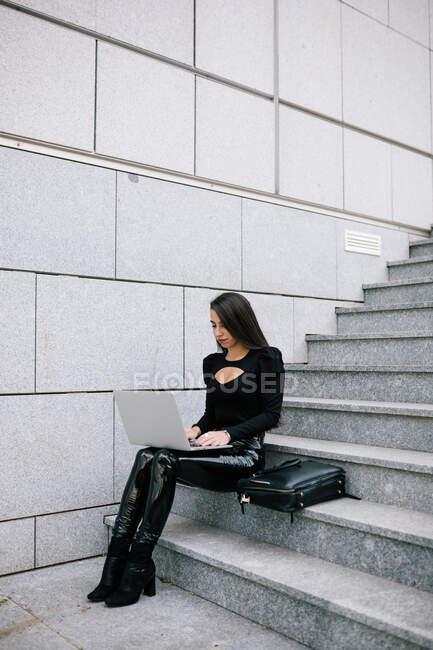 Сторона зору сфокусованої жінки-підприємця сидить на кам'яних сходинках у місті і переглядає нетбук під час роботи над проектом онлайн — стокове фото