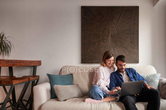 Cheerful young multiracial couple in casual outfits smiling while sitting on sofa and having video conversation via laptop — Stock Photo