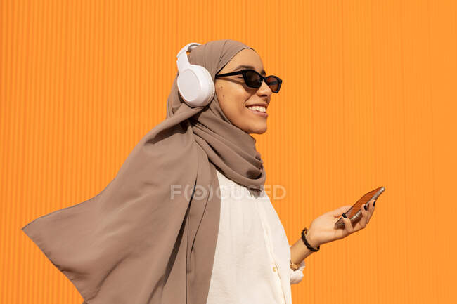 Side view of sincere ethnic female in headscarf and wireless headphones with cellphone listening to music in daylight — Stock Photo