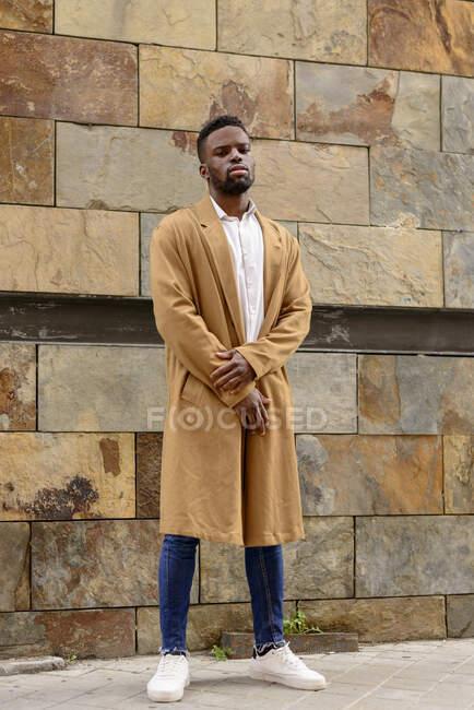 Ganzkörper-Afroamerikaner in modischem Mantel steht in der Nähe einer Steinmauer in der Stadt und blickt in die Kamera — Stockfoto