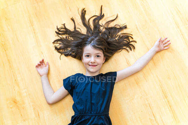 Top view delighted little girl lying on parquet with hair and arms outstretched and laughing happily while looking at camera — Stock Photo