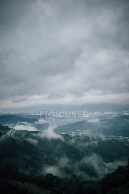 Picturesque view of majestic mounts with green woods under cloudy sky in misty weather — Stock Photo