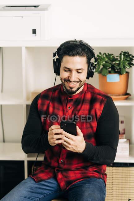 Доросла людина боролася з музикантом у навушниках, спілкуючись по мобільному телефону у вітальні. — стокове фото