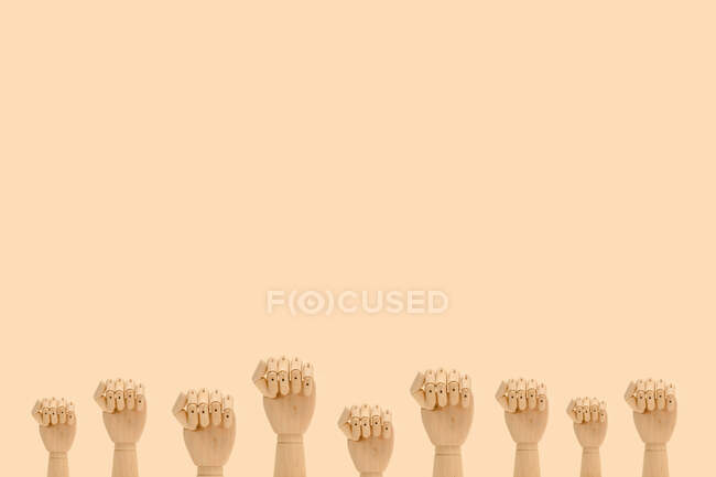 Minimalistic composition of wooden hands demonstrating fists as symbol of protest placed against beige background — Stock Photo