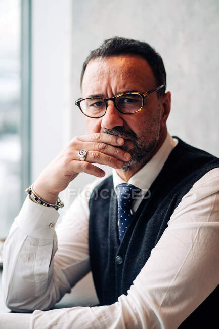 Middle aged ethnic male boss in eyeglasses and formal clothes touching mouth while looking at camera — Stock Photo