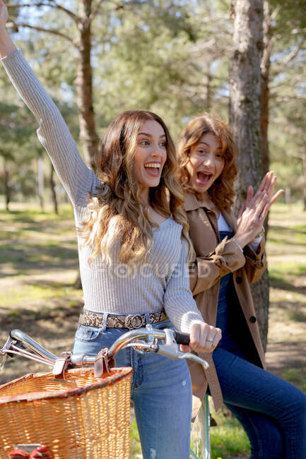 Happy young girlfriends smiling and looking at camera on bicycle in sunny park in summer — Stock Photo