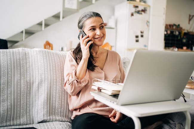 Concentrated middle aged female having phone call and taking notes in notepad while looking at screen of laptop in light room at home — Stock Photo