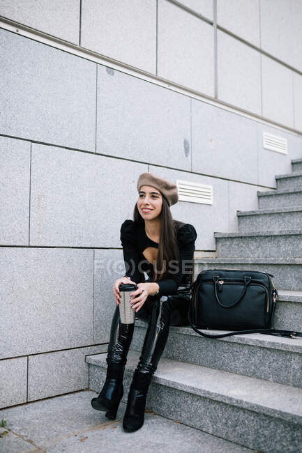 Delighted stylish female entrepreneur in trendy outfit and beret hat sitting on stairs with beverage to go in city and looking away — Stock Photo
