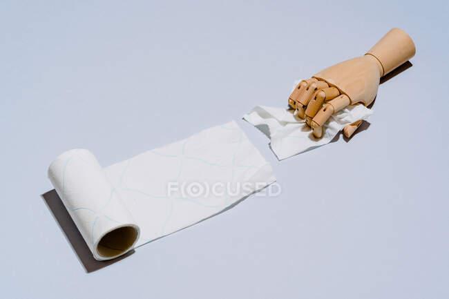 Composición de manos de madera desenrollando rollo de papel higiénico blanco sobre fondo azul - foto de stock