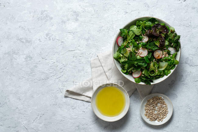 Vista superior de la ensalada de verduras frescas y saludables en un tazón servido en la mesa con aceite de oliva y semillas de girasol - foto de stock