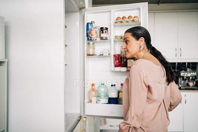 Vista lateral da fêmea calma com porta de abertura de rabo de cavalo da geladeira com vários produtos enquanto está em pé na cozinha com armários brancos — Fotografia de Stock