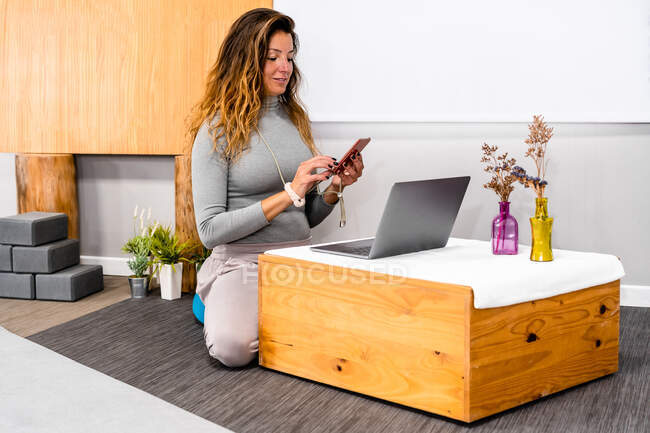 Content young female with long hair in casual clothes messaging on smartphone while working remotely on laptop sitting on floor at small wooden table in minimalist apartment — Stock Photo