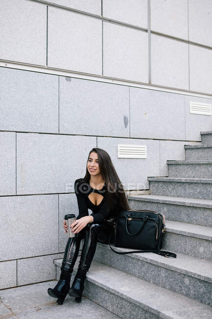 Delighted female entrepreneur in trendy outfit sitting on stairs with beverage to go in city and looking away — Stock Photo