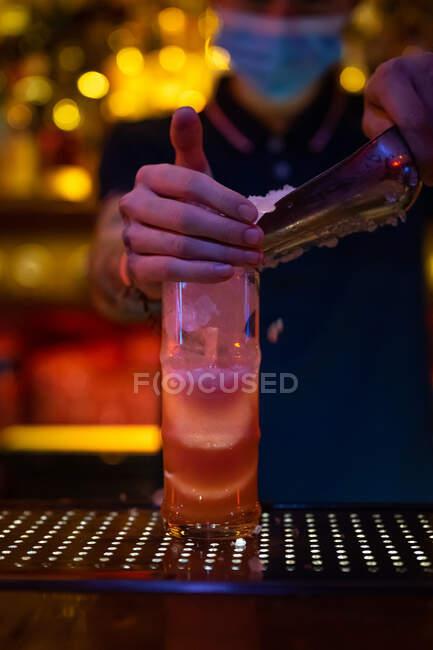 Руки нерозпізнаного бармена під час підготовки коктейлю в барі втискають лід у чашку. — стокове фото