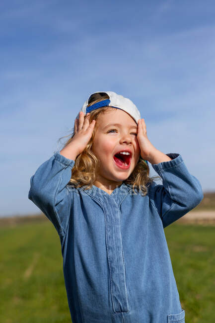 Happy blond girl in cap touching head and looking away with opened mouth against blue sky in summer in meadow — Stock Photo